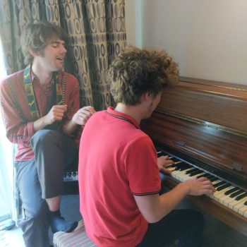 two male musicians playing piano and singing at summerhouse recording studios